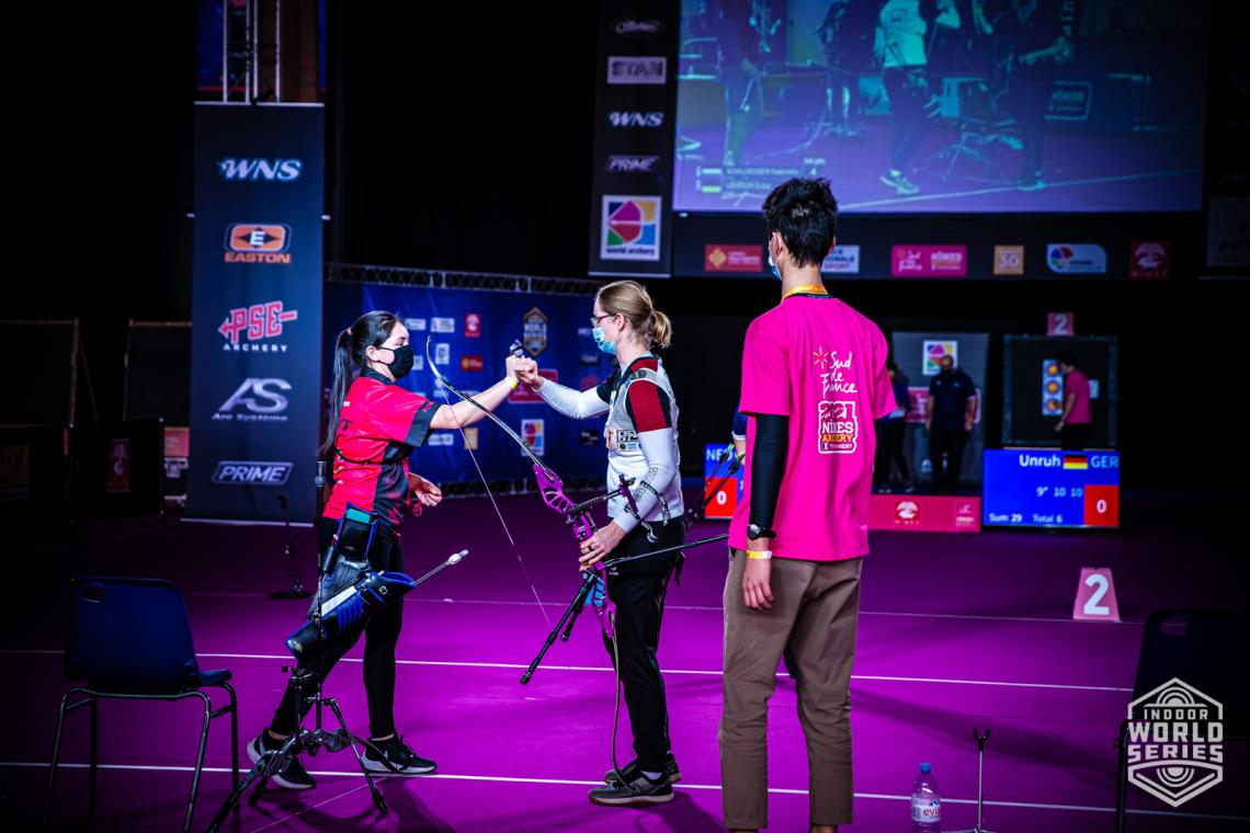 Gaby Schloesser and Lisa Unruh fist-bump during the finals at the Sud de France – Nimes Archery Tournament in 2021.